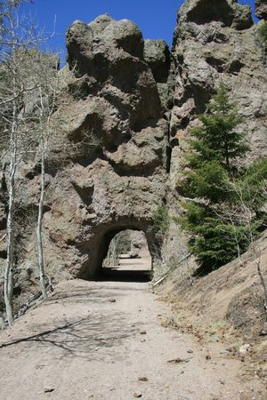 tunnel through a rock outcrop for a single lane dirt road Stock Photo - 3891180