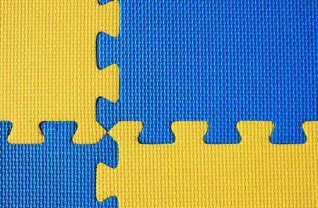 interlinked: entrelazados de color azul y amarillo acolchado ni�o juegue esteras de fondo Foto de archivo