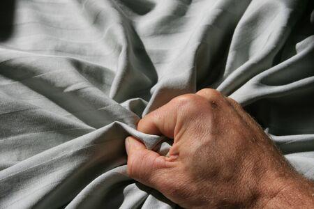 mans hand grabbing a crumpled striped bed sheet