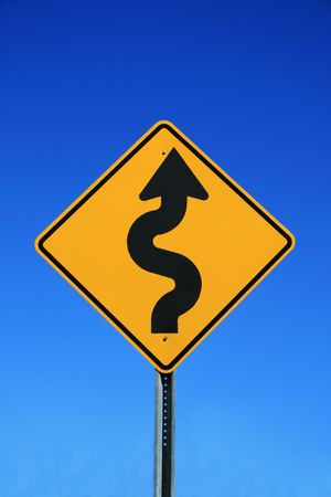 winding road sign in yellow and black on blue sky background photo