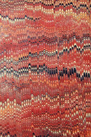 red, yellow, and black marbled paper from an antique book