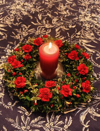 red lit candle surrounded by red and green decoration on a table top Stock Photo - 4015354