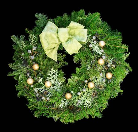 Christmas wreath with gold balls and pale green ribbon on dark background