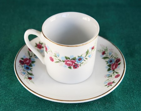 antique teacup and saucer on a green background photo