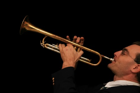 man plays a trumpet with a black background