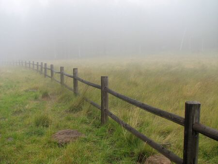 a wooden fence fades into the fog with a ghostly forest in the distant Stock Photo - 4064620