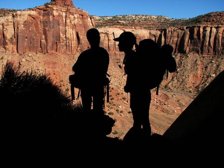 indian creek: silhouette of 2 backpackers in front of red sandstone cliffs in Utah Stock Photo
