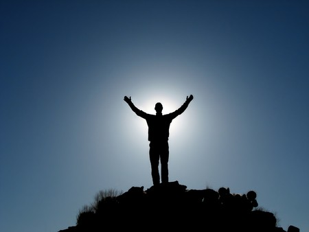 upraised: Silhouette of man on a summit with upraised arms backlit with the sun Stock Photo