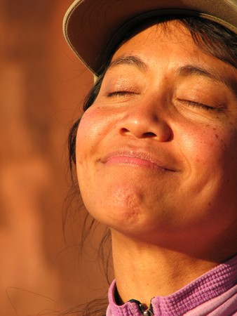 mid afternoon: face of Asian woman basking in the last light of the day with her eyes closed