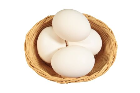 4 white eggs in a small wicker basket isolated on white photo