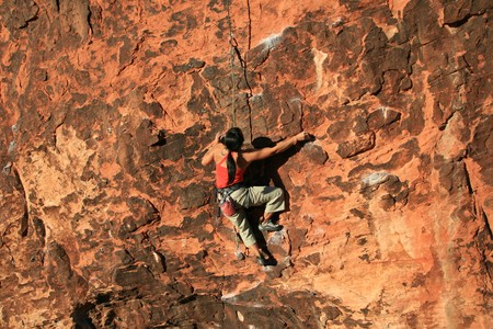 rockclimb: woman rock climber in red climbing a red sandstone cliff at Red Rocks, Nevada