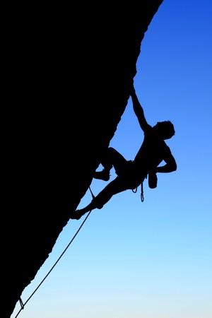 stijger: silhouet van de rots klimmen klimmer een overhangende klif met blauwe hemel achtergrond
