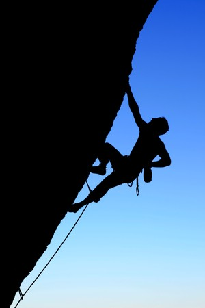 rockclimber: silhouette of rock climber climbing an overhanging cliff with blue sky background