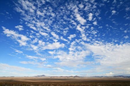 big sky in the desert with clouds and empty plains leading to distant mountains