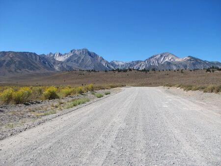 extends: rural road extends towards distant mountains  Stock Photo