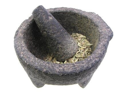 Mexican stone mortar and pestle with spices isolated on white