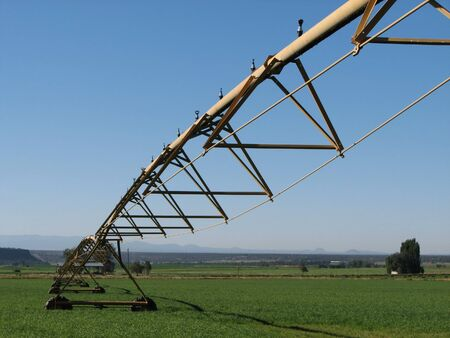 view from under a pivot irrigation system in a green field Stock Photo