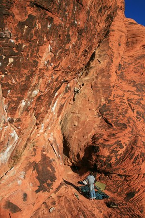 belaying: two sport climbers on red rock sandstone, one belaying