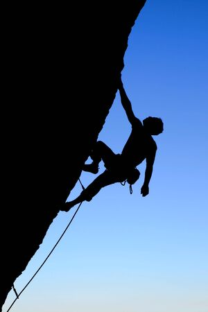 cling: silhouette of rock climber climbing an overhanging cliff with blue sky background