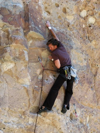 rock climbing man leading on welded tuff, New Mexico