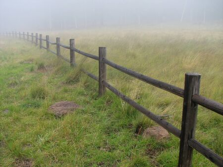 a wooden fence fades into the misty distance on a foggy day Stock Photo - 4422972