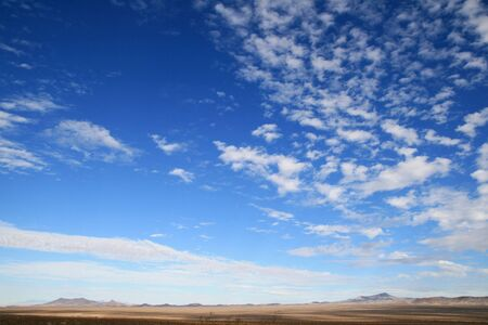 big sky country in the desert with clouds and empty plains leading to distant mountains