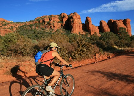 an Asian woman mountain biking along a dirt road near Sedona Arizona