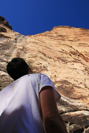 a male rock climber looks up at a cliff at Red Rocks in Nevada