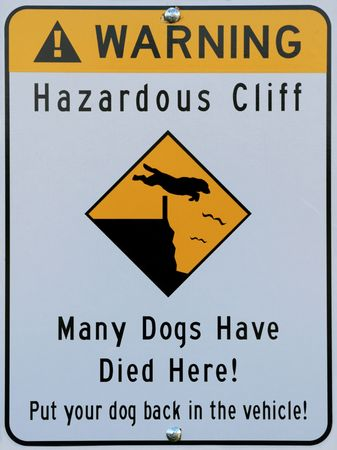 hazardous cliff warning sign showing a dog jumping over a fence and over a cliff photo