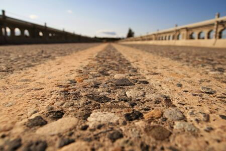 view from very close to the pavement in the center of the roadway on a bridge with very shallow depth of field Stock Photo - 4731407