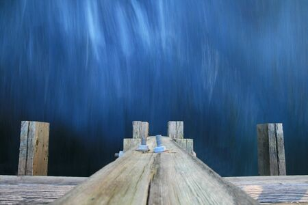long exposure of water flowing under a wooden bridge with motion blurred water Stock Photo - 4764519