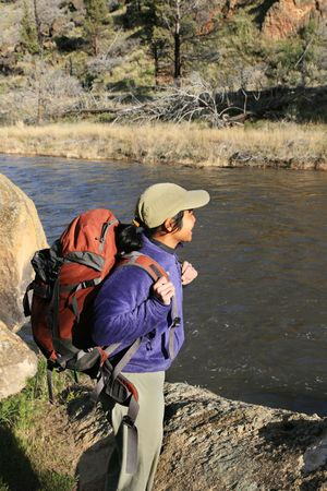 side view of a woman backpacker standing on a rock next to a river
