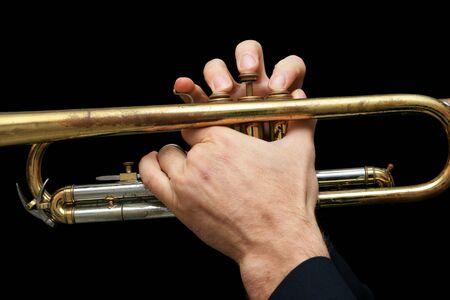 暗い背景とトランペットを演奏、人間の手の詳細