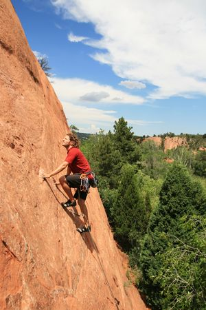 rockclimber: a man in red leading on a sandstone slab rock climb Stock Photo