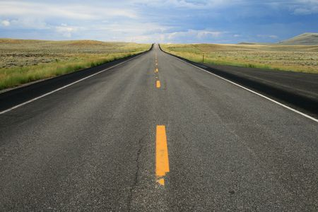 a car crests the distant hill on an empty road in Wyoming Stock Photo