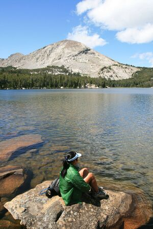 a woman in a green jacket sits on a rock by alpine Silas Lake in the Wind River Range, Wyoming Stock Photo - 5324777