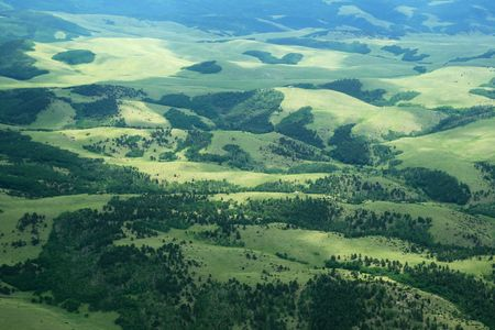 aerial photo of hills in Colorado with green fields and trees