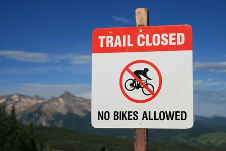 trail closed no bikes allowed sign on a downhill trail in Telluride, Colorado with out of focus mountains in the background