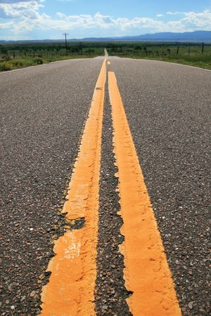 the yellow lines of a rural Colorado road lead off towards the distant horizon Stock Photo - 5447146