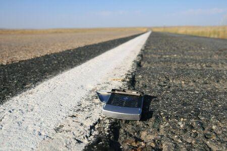 gebrochen �berfahren Handy auf der Stra�e mit selektiven Fokus