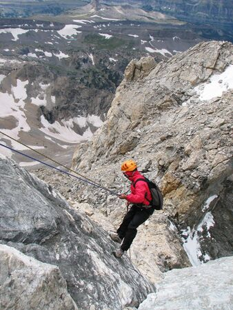 rappeling: a woman mountaineer rappelling off of the Grand Teton, Wyoming