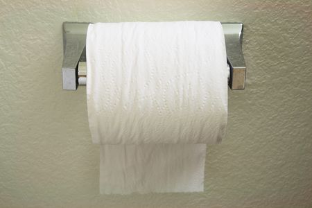 a toilet paper roll dispenser with the paper feeding over the top towards the back Stock Photo