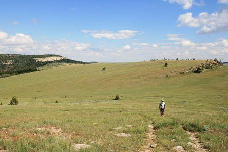 woman walking away across a high meadow at Wild Iris area of Limestone Mountain, Wyoming Stock Photo - 5582490