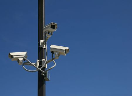 three security video cameras mounted on a pole with a blue sky background and copy space Stock fotó