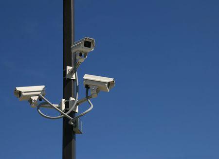 paranoia: tre videocamere di sicurezza montato su un palo con uno spazio di sfondo e copia di cielo blu