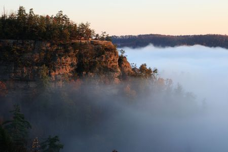 sandstone: a sandstone cliff rises above early morning fog in the autumn Stock Photo