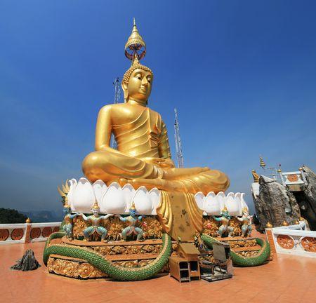 Wat Tham Seua or Tiger Cave Temple mountain top golden Buddha statue, Krabi, Thailand