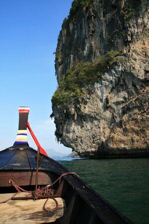 railey: una prua di barca Thai lunga coda come si passa a una scogliera calcarea vicino a Krabi, Thailand