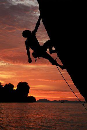 바다 배경 위에 석양 돌출 된 절벽을 등반하는 바위 산악인의 실루엣 스톡 콘텐츠