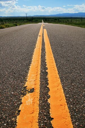 yellow lines on a rural road heading into the distance